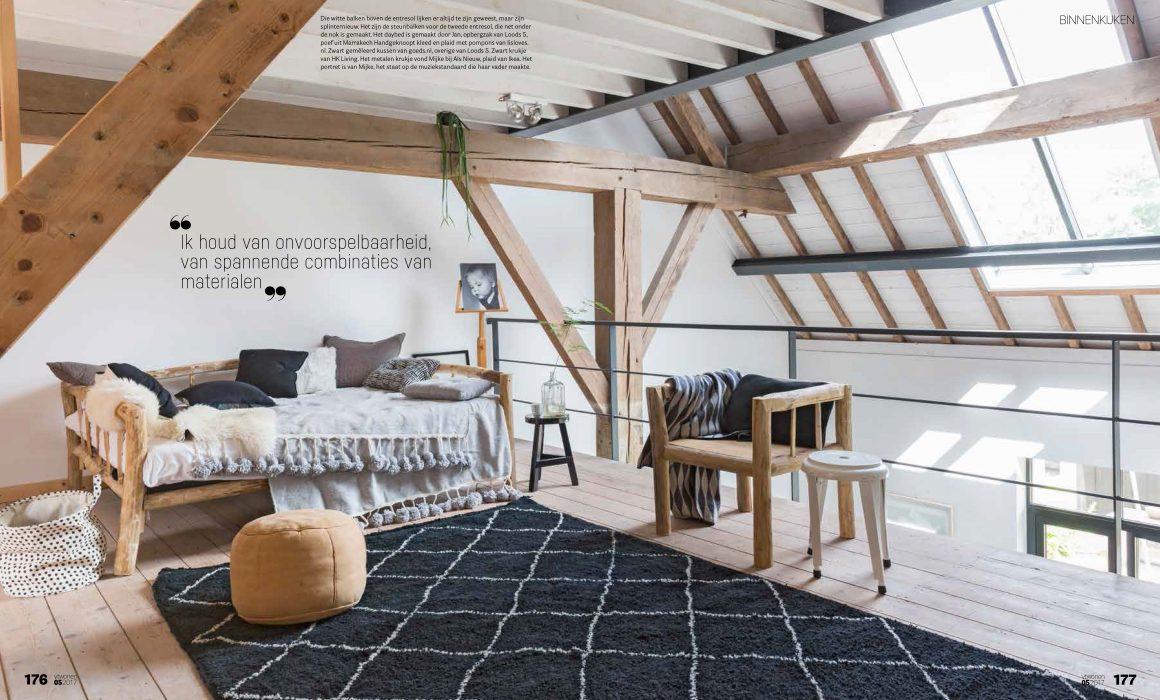 Zolderverdieping met daybed en groot vloerkleed op de voorgrond.