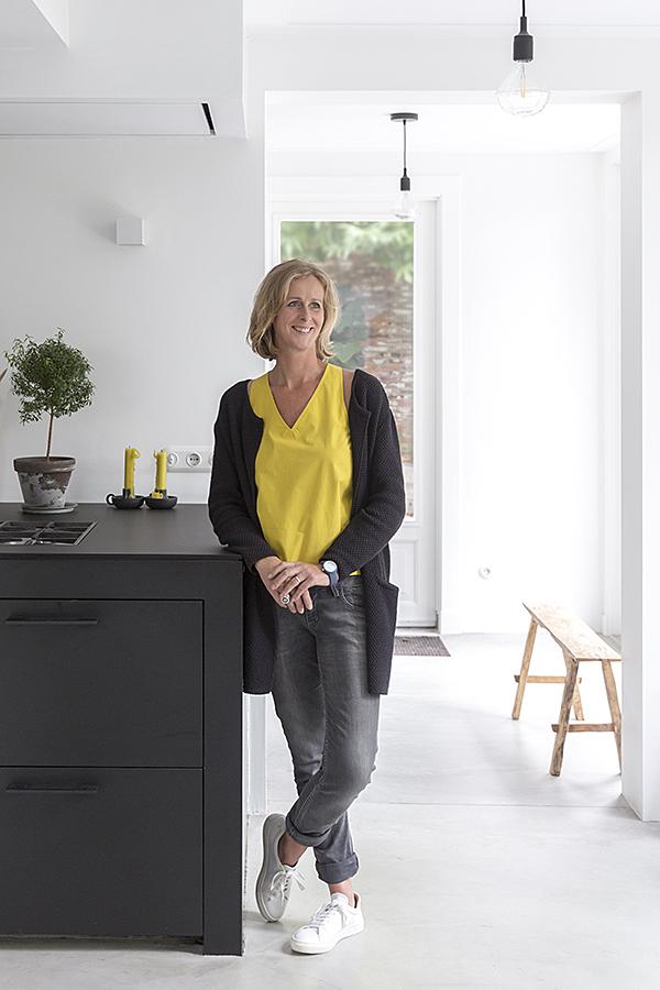 Portret van Jolanda Diks geleund tegen een zwarte keuken