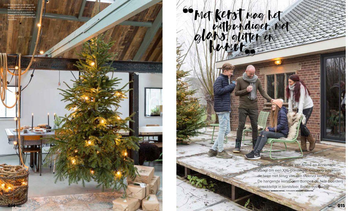 Een kerstboom met lichtjes erin hangend aan een touw in de woonkamer